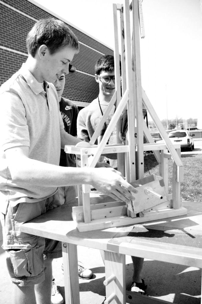 Below, seniors from an Industrial Design class demonstrate how to use a trebuchet (catapult) that they built. Photo by Megan Engleman.