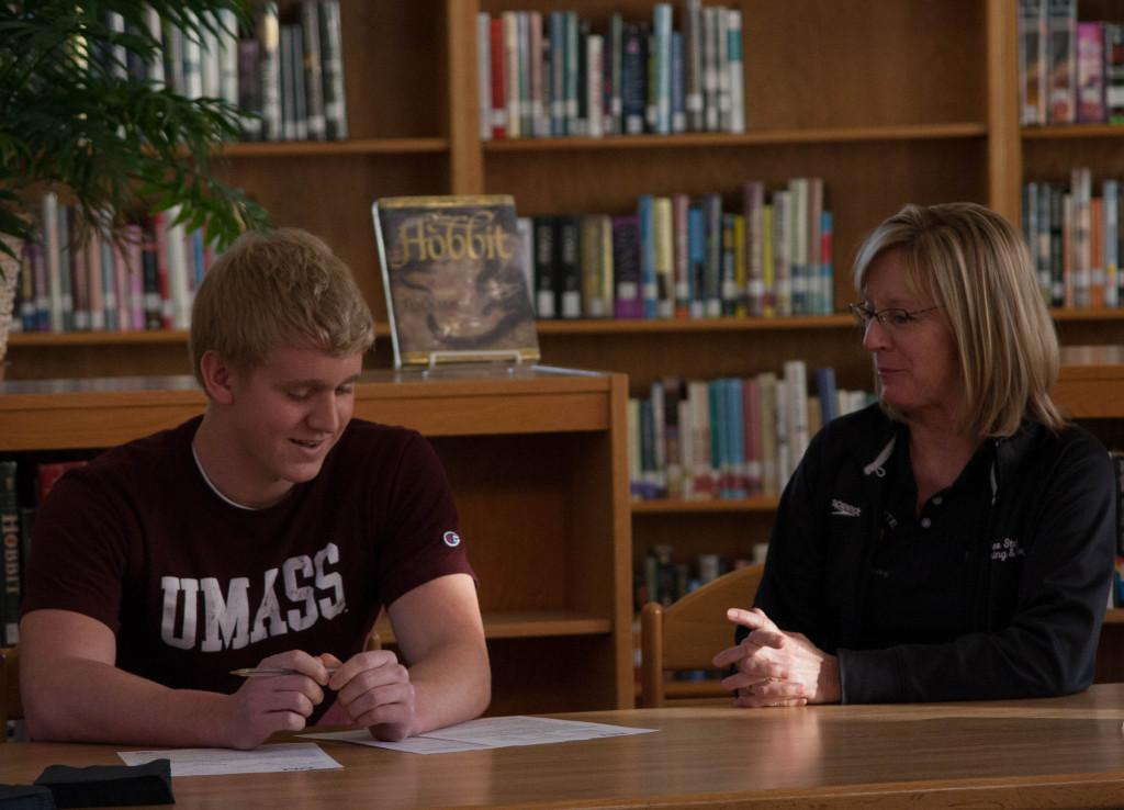 Senior Ben Sloan signs to swim at the University of Massachusetts in the Free State library in December. Coach Annette McDonald looks on from his side.
