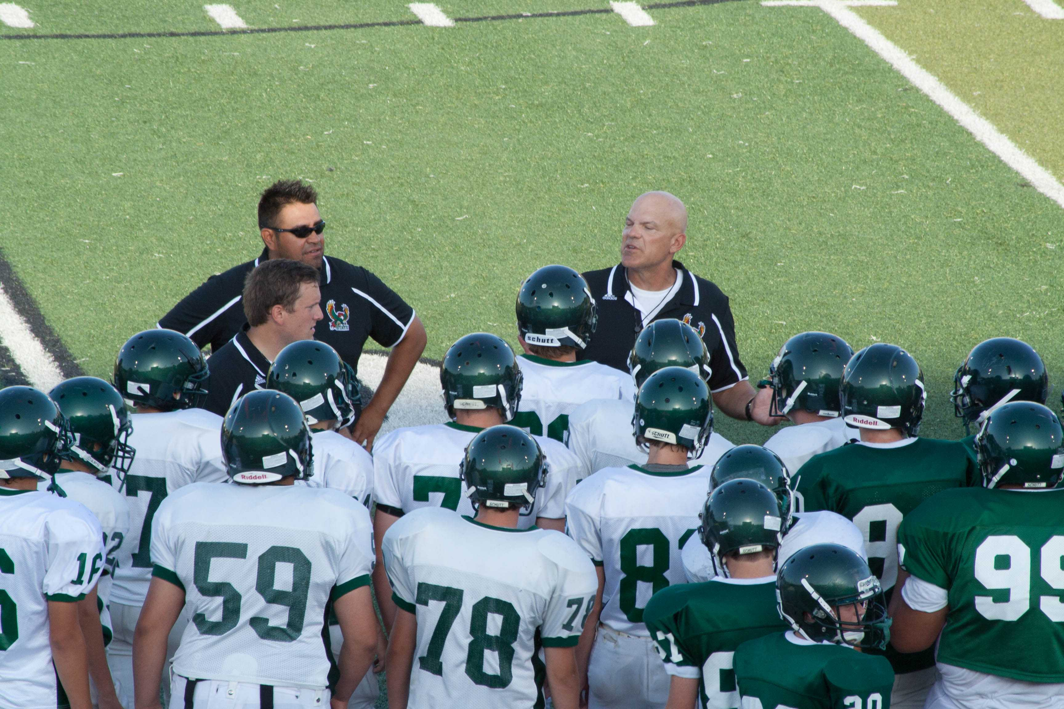 The+football+coaches+give+the+team+a+pep+talk+during+a+break+in+the+scrimmage.+