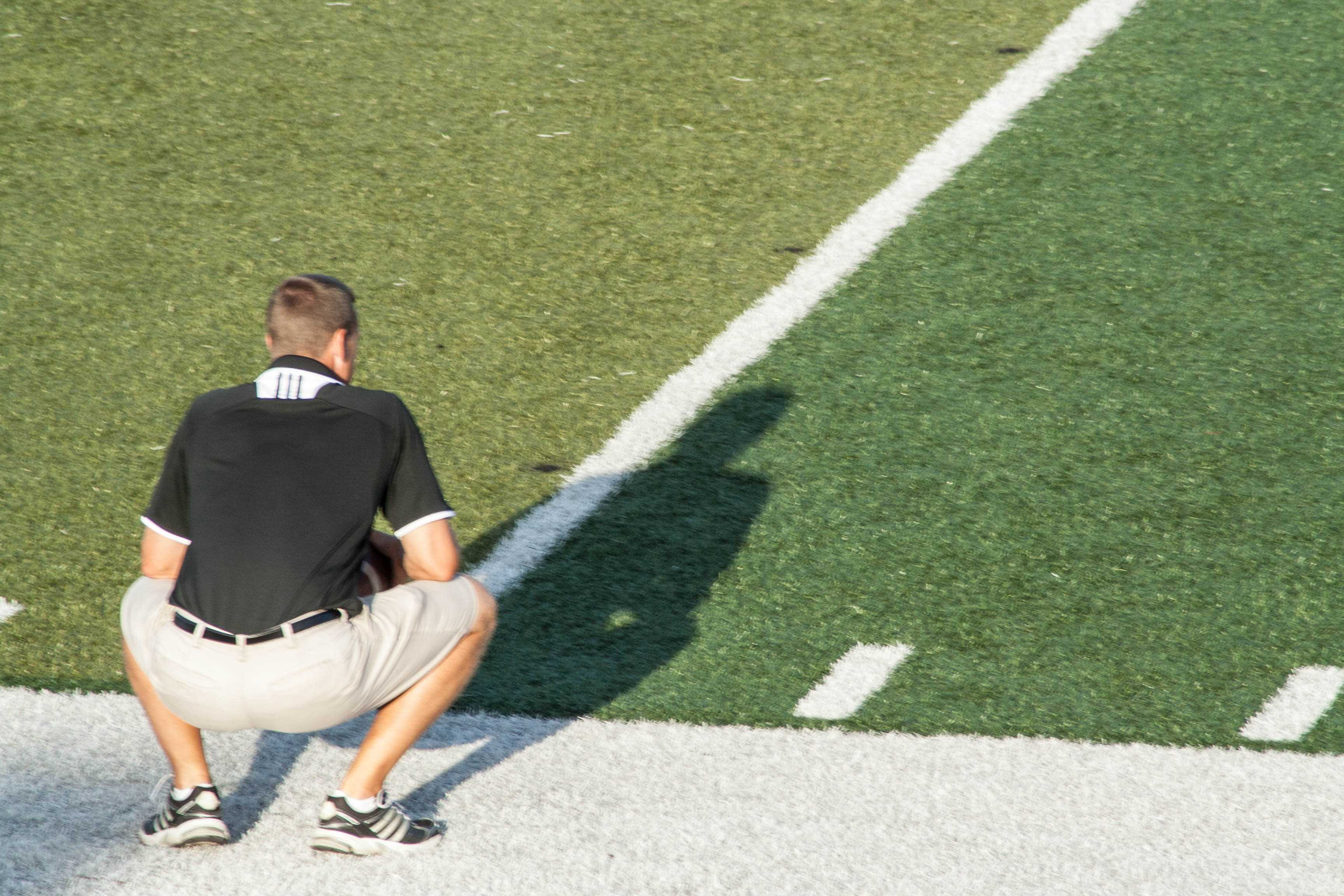 A+football+coach+crouches+down+as+he+watches+his+team+scrimmage.+