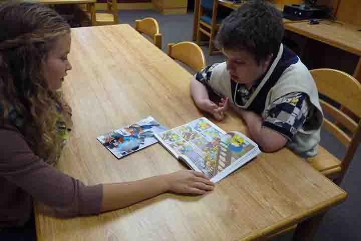 Reporter Fiona McAllister reads a Simpsons comic book with freshman Benji Horton.