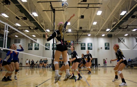 Senior Sydney Moreano and sophomore Payton Gannaway jump to block a spike from Bishop Miege during a match on Oct. 15.