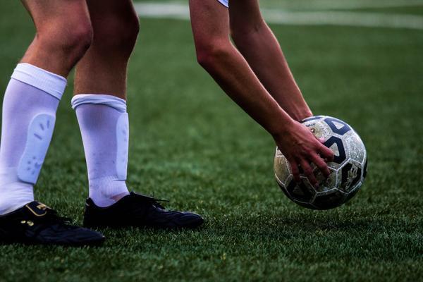 Varsity soccer player places the ball for a penalty kick at a home game during the fall season.