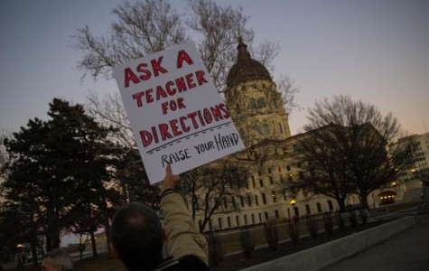 A member of KNEA holds up a sign during a protest at the capitol in Topeka. Sam Brownback's plan to cut school funding resulted in marches and protests.