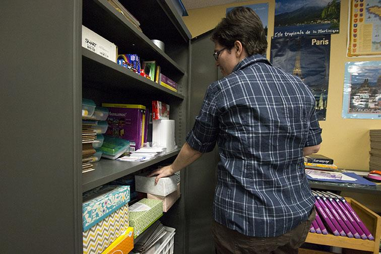 Opening her classroom cabinet, French teacher Karen Gipson, checks her Kleenex supply. Gipson has never rewarded her students with extra credit for turning in tissues.