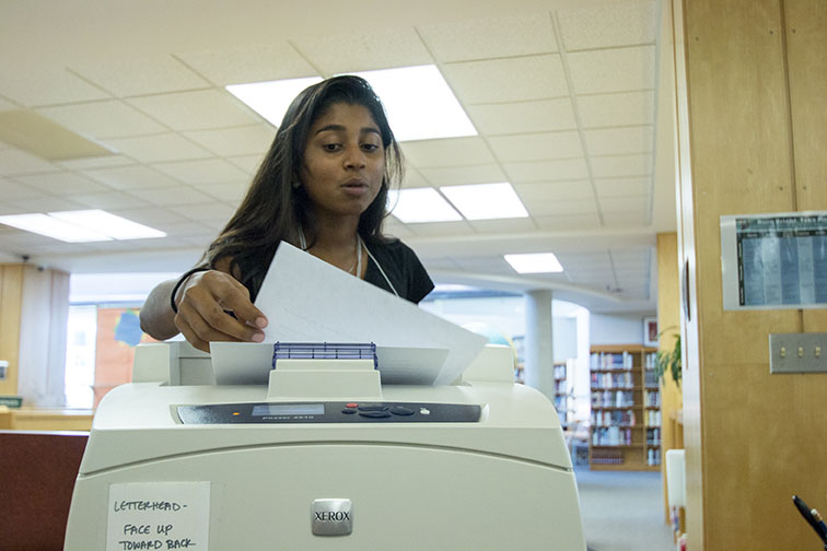 Finding an assignment for class, senior Isabel Marshall-Kramer picks up her paper at the librarys printer. The library printer offers free printing to all students. Conscious of funding, teachers have been asking students to print from home, if possible.