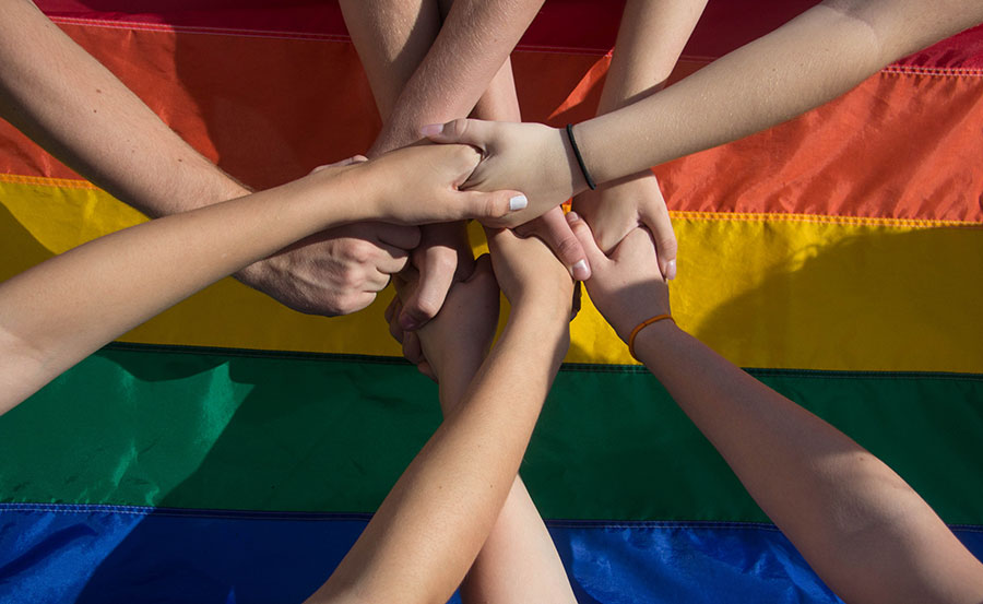 Gay couple holding hands in front of a rainbow flag