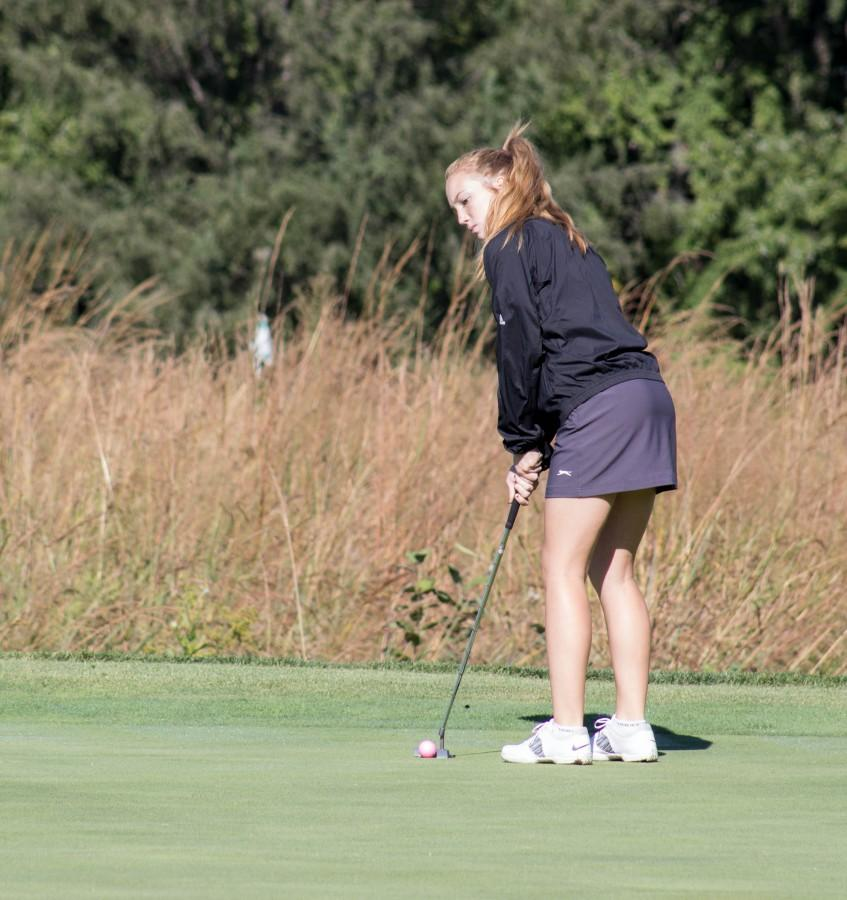 Watching competitors read their putt, sophomore Tori Hoopingarner waits to move onto the next hole. Hoopingarner first got interested in golf because of her dad and grandpa, They were really into golf, so I tried it out and I liked it, Hoopingarner said.