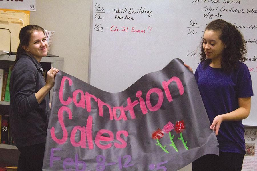 Prepping for their Valentines Day carnation sales, junior Katie Lane and freshman Tylee Harrell display their recently finished banner.