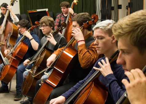 Making music, sophomore Teagan Ryan plays his cello alongside his classmates. Ryan is in concert orchestra, under the direction of one of the new music teachers, Mr. Shaw.