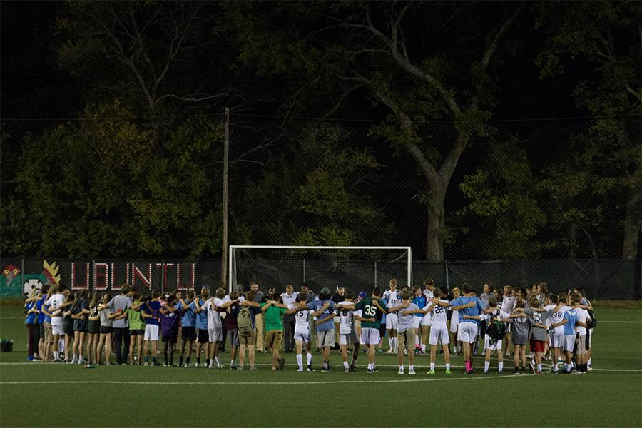 The varsity soccer team performs their ceremonial huddle after a home game. Fans and parents were encouraged to join.