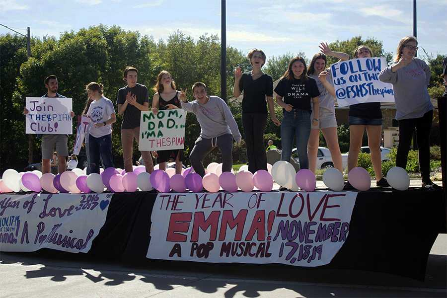 Eli Bork, Anna Bial, Chris Pendry, Morgan McReynolds, Ilya Schaeffer, Calliope Taylor, Rheanne Walton, Anina Supernaw, Helena All, Eliza Hasse-Divine hold signs and cheer towards spectators during the homecoming parade. There were hundreds of spectators during this years parade.