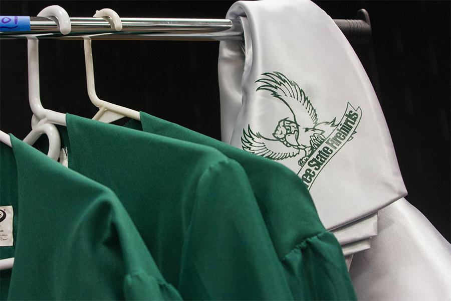 Gowns sit on a hanger in the Black Box. Seniors can avoid additional fees by using their siblings garments.