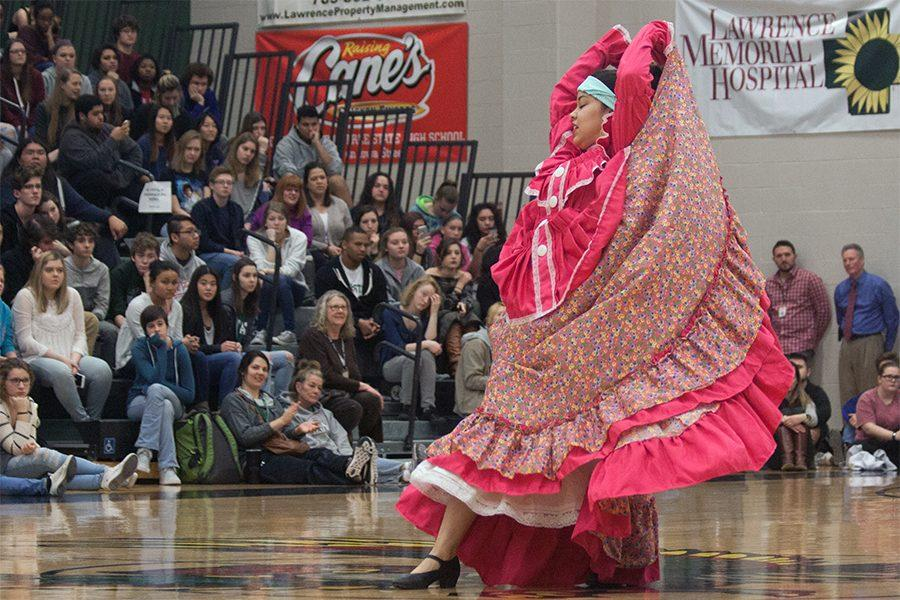 Raising her arms, sophomore Mariela Martinez performs El Ardillo. The diversity assembly was on Feb. 2 in the big gym.