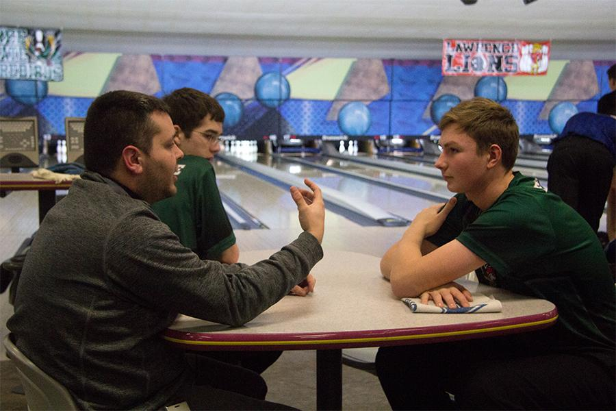 Listening+to+his+coach+Nick+Campfield%2C+sophomore+Bayn+Schrader+discusses+his+bowling+strategy.+Schrader+joined+the+boys+varsity+bowling+team+freshman+year+and+has+lettered+both+years.+%E2%80%9CI%E2%80%99ve+done+the+high+school+leagues+through+Royal+Crest+in+the+summer+since+sixth+grade+and+I%E2%80%99ve+been+bowling+since+I+was+nine%2C%E2%80%9D+Schrader+said.