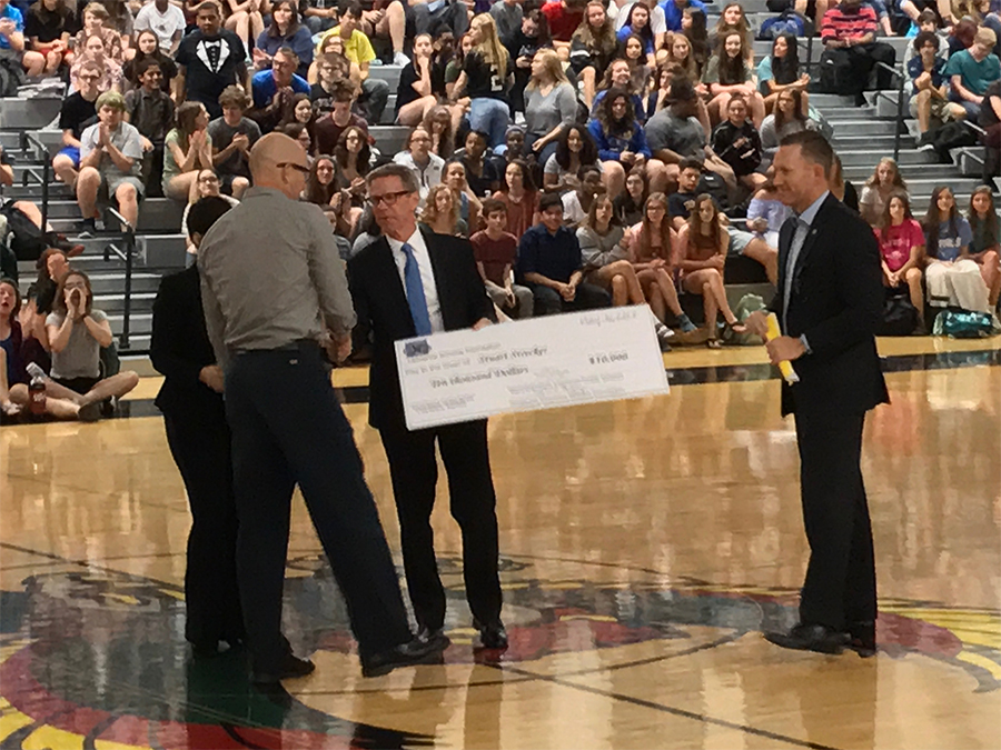 Stuart Strecker receives the $10,000 check from Lawrence Schools Foundation board of director's president Scott Morgan. This year is the Bobs Award twentieth anniversary.