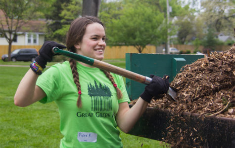 "Shoveling mulch, junior Piper Rogers fills up wheel barrells to be carried to flower beds. Around 100 juniors volunteered for Great Green Help. ""My favorite part was seeing all of the smiles and hard work that people put in despite the rain,"" Rogers said."