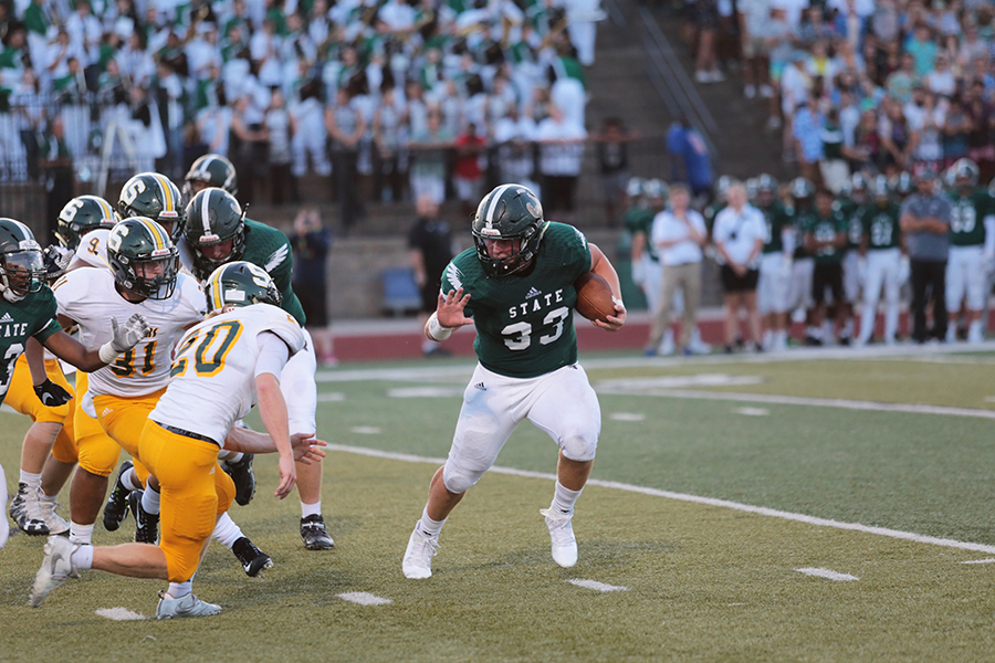 Junior Jax Dineen tries to avoid his opponent. Dineen scored multiple touchdowns.