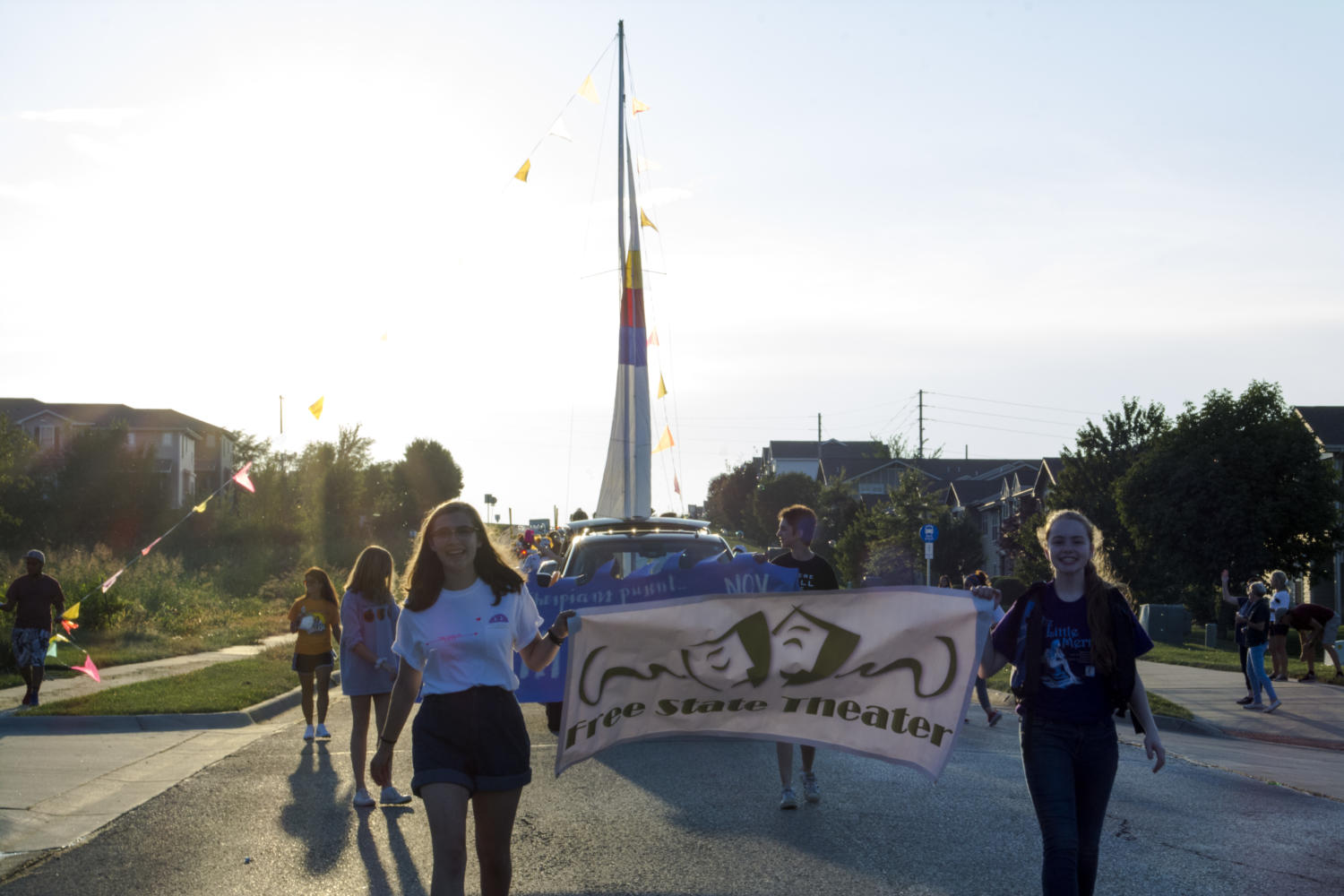 Junior Sophie Johnson and freshmen Emily Bial carry the Free State Theater banner in the homecoming parade. A float for the musical