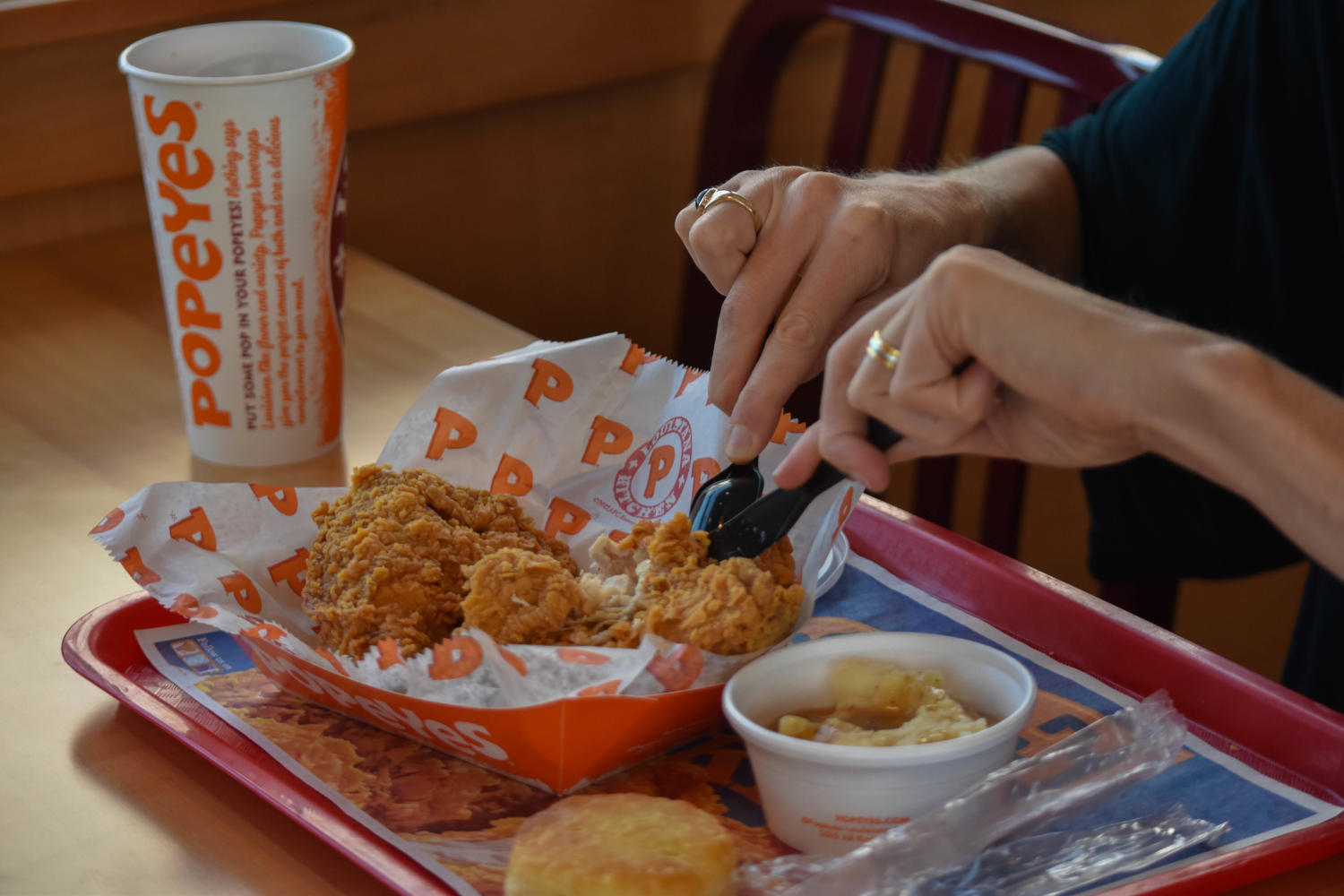 A woman cuts into her chicken at Popeyes Louisiana Kitchen.