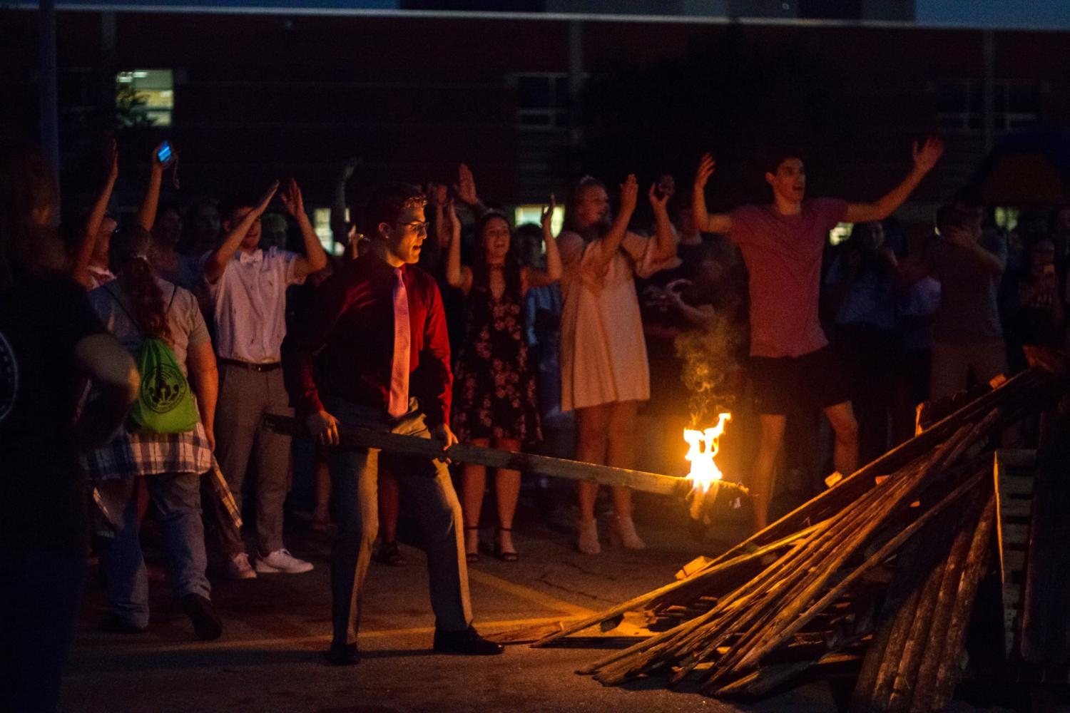 Homecoming candidate Teddy Carttar attempts to light the fire. Due to the wood being wet, the fire was unable to remain lit.