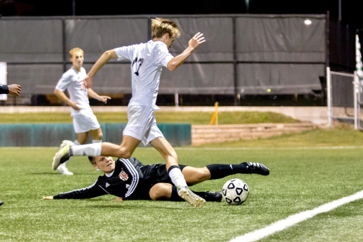 Junior Landon Sloan avoids slide tackle from opposing defender. Sloan was out in the first overtime due to a cramp in his leg.