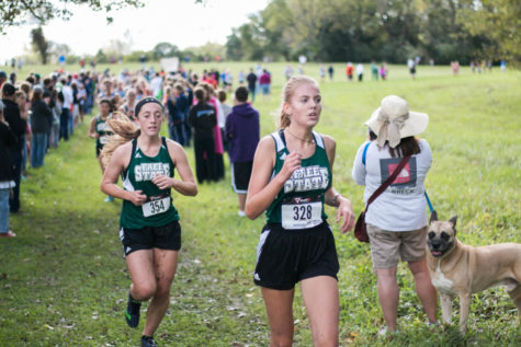 Sophomore Bella Crawford-Parker and senior Kate Odgers run past a dog. Crawford-Parker finished in 23:38.