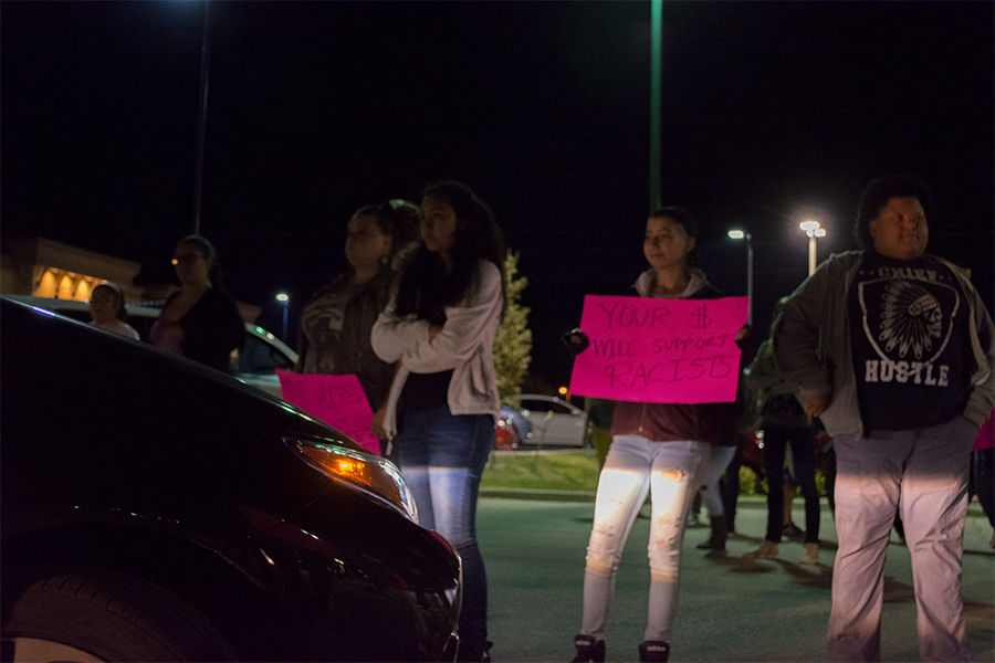 Sophomore Ashton Mcknight and fellow protestors block a car from entering the Burger King parking lot. The car eventually forced its way through, but left immediately afterwards.