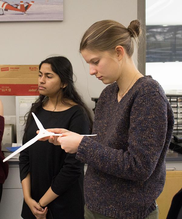 Senior Sandhya Ravikumar listens to a presentation while senior Carlee Oliver examines a model turbine's blades.