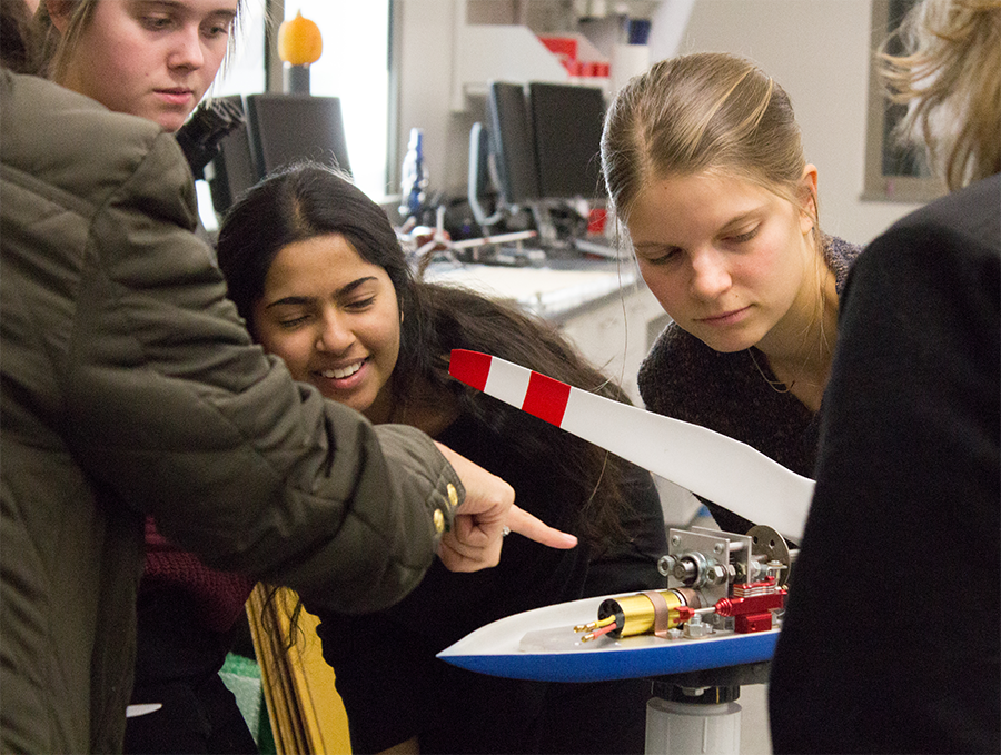Ascent club members are shown a model wind turbine during a field trip.