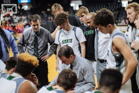 With players and coaches gathered around, boys basketball coach Sam Stroh discusses strategies for the fourth quarter. Simon McCaffrey hit two free throws at the end of the game to help ensure Free State finished with a win.