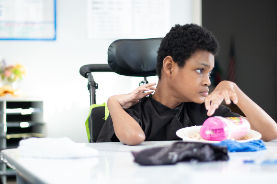 """Junior Dorian Horton eats lunch at a new desk. SpEd teacher Marie Wheeler described how teachers had to be creative in making the space comfortable for students. """"It was a struggle at first but it is definitely [an improvement],"""" Wheeler said."""