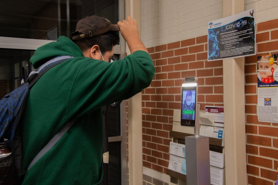A student checks their temperature in the front office so they can be cleared to enter the school and start their day. At the beginning of each day, every student is required to check their temperature to ensure that students are staying healthy. There is least one temperature station per entrance to make sure all students are checked in before they enter the building.