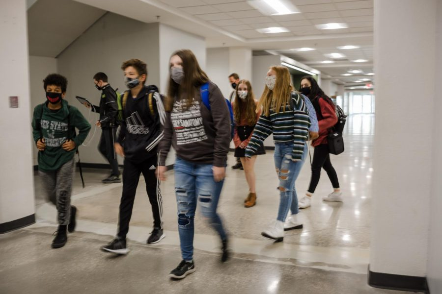 Walking through the halls, a group of students heads to their next class. The hybrid plan began in late October, and continues phasing-in to allow more students to attend in-person classes.